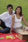 A couple smile at the camera as they have a picnic together in the park - Asia Images Group