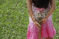 A small girl holds flowers behind her back - Asia Images Group