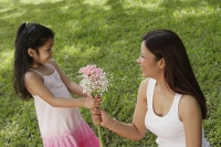 A young girl gives her mother a bunch of flowers - Asia Images Group