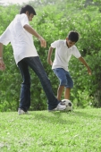 A father and son play soccer together - Asia Images Group