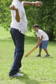 A father and son play cricket together - Asia Images Group