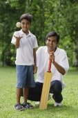 A father and son look at the camera as they play cricket together - Asia Images Group