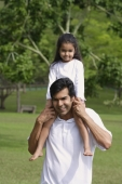 A father carries his daughter on his shoulders as they both look at the camera - Asia Images Group