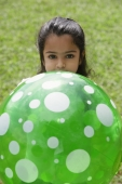 A small girl plays with a green ball - Asia Images Group