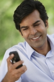A man smiles as he checks his cellphone - Asia Images Group