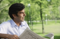 A man reads the newspaper in the park - Asia Images Group