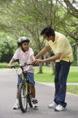 A father teaches his son to ride a bike - Asia Images Group