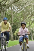 A father and son ride their bikes together - Asia Images Group