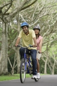 A couple ride a bike together - Asia Images Group