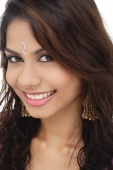 A young woman with a bindi smiles at the camera - Asia Images Group