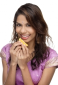 A young woman smiles at the camera as she eats a slice of orange - Asia Images Group