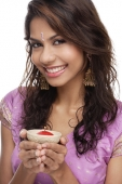 A young woman smiles at the camera as she holds a candle - Asia Images Group