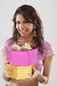 A young woman smiles at the camera as she holds gifts - Asia Images Group