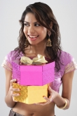 A young woman smiles as she holds gifts - Asia Images Group