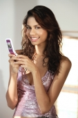 A young woman smiles at the camera as she uses her cellphone - Asia Images Group