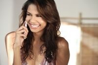 A young woman smiles as she talks on a cellphone - Asia Images Group