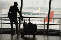 Man watching planes at airport - Asia Images Group