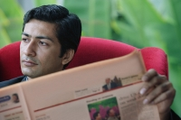 Man reading financial newspaper - Asia Images Group