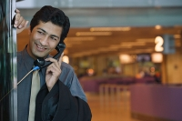 Man talking on pay phone - Asia Images Group