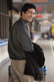 Man pushing trolley in airport, smiling at camera - Asia Images Group