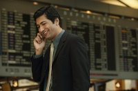 Man talking on the phone at airport - Asia Images Group