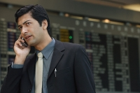 Man talking on phone at airport - Asia Images Group