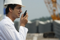 Man in work uniform, talking into walkie talkie - Asia Images Group