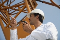 Man in work uniform pointing and using walkie talkie - Asia Images Group