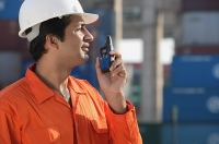 Man in work uniform using walkie talkie - Asia Images Group