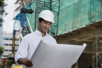 Man with helmet, looking at plans - Asia Images Group