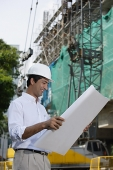 Man smiling while looking at plans - Asia Images Group