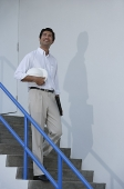 Man smiling while walking down stairs - Asia Images Group