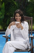 Woman in chair with cup, smiling at camera - Asia Images Group