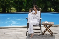 Woman in chair by the pool, holding bowl of cereal and looking at camera - Asia Images Group