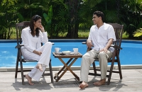 Couple sitting by the pool, looking at each other - Asia Images Group