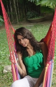 Woman in hammock, looking at camera - Asia Images Group