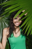 Woman hidden by plants, smiling at camera - Asia Images Group