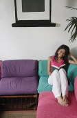 Woman sitting on sofa, reading a book - Asia Images Group