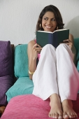 Woman on sofa with book, smiling and looking sideways - Asia Images Group