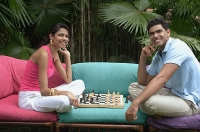 Couple playing chess outdoors, smiling at camera - Asia Images Group