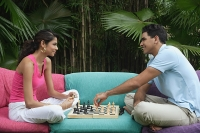 Couple playing chess outdoors - Asia Images Group
