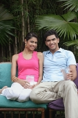 Couple on chairs outdoors, smiling at camera - Asia Images Group
