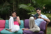 Couple reading on sofa outdoors - Asia Images Group