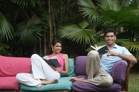 Couple sitting on sofa outdoors, smiling at camera - Asia Images Group