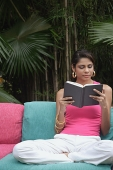 Woman of sofa reading book outdoors - Asia Images Group