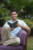 Man with book on chair, smiling at camera - Asia Images Group