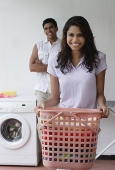 Woman doing laundry and smiling at camera - Asia Images Group