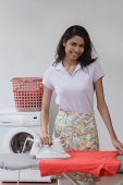 Woman ironing shirt and looking at camera - Asia Images Group