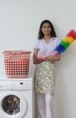 Woman with feather duster, looking at camera - Asia Images Group