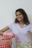 Woman with rubber gloves and washing basket, smiling at camera - Asia Images Group